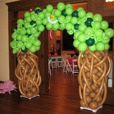 Tree archway with Cheshire Cat from Alice in Wonderland entrance. Make the majority of the balloons the deeper green for a darker feel. Also if we can't find a darker brown to mix in, use a brown Sharpie to add some depth of color on the trunks.
