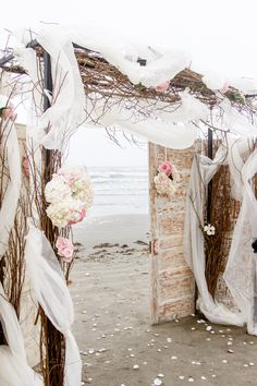 Romantic beach wedding arch.  I could see this in the woods or a beautiful garden. Old doors and  branchy garland.