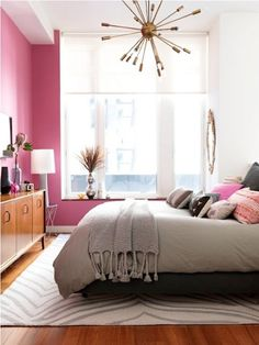 Mid Century modern bedroom with brass sputnik pendant light, pink walls & retro sideboard