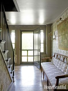 A pearlescent glaze, Benjamin Moore's Shyness, bounces light down the entry hall.