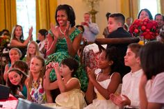 First Lady Michelle Obama and guests applaud as Big Time Rush performs during the Kids' State Dinner in the East Room of the White House, Aug. 20, 2012.