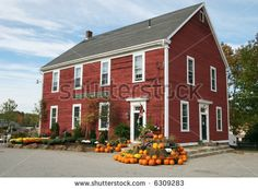 stock photo : old red farmhouse with pumpkin and mum display