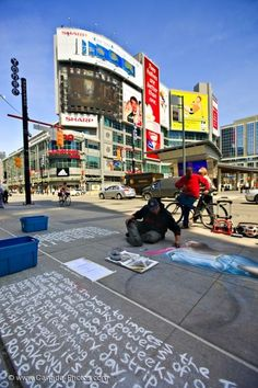 Artist draws with chalk on the pavement  in downtown Toronto City, Ontario, Canada.