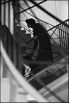 Paris 1958 - Coco Chanel, hiding in a stairway, watching her own fashion show through a mirror, unaware  of the photographer who watches her through another mirror.