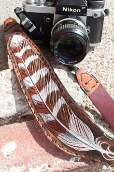 Tooled leather feather camera strap.