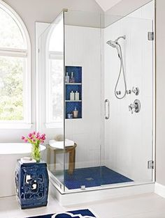 For a walk-in shower with classic style, incorporate a blue and white color scheme. Navy blue hues repeat on this shower's floor tile and shelving backsplash. Glass walls on two sides of the corner shower make the bathroom feel larger and welcome light from a nearby window.