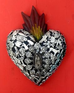 Mexican Milagro Sacred Heart decorated with milagros.