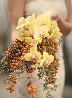 A semi- cascading bridal bouquet composed of mini dates, seeded eucalyptus, and cream margarita orchids wrapped in a cotton cream colored ribbon. Floral Design: Felipe Sastre, Brooklyn, NY; Photography: Rob Langhammer, New York, NY