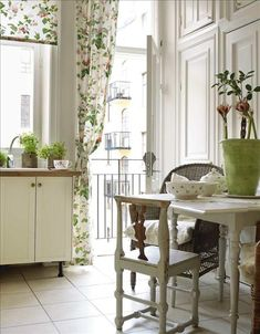 Beautiful floral fabric and green plants bring a country feel to this city apartment kitchen in  Sweden.