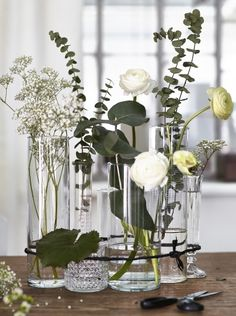 For a modern twist on the traditional flower arrangement, group a variety of clear glass vases with randomly placed flowers together and bind with twine.