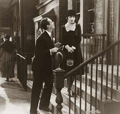 "Clara-Bow wearing the famous DIY little black dress by designer Travis Banton in the hit 1928 film ""IT"". In a memorable scene, Bow takes a scissors to her day suit and transforms it into an evening frock."
