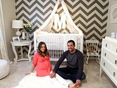 Picture of parents sitting on the floor in the nursery, holding new baby.