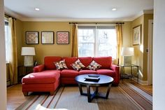 A red couch mixed with warm living room colors. And wow - that is the color of my living room walls!