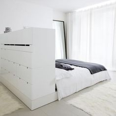 Headboard / room divider and storage in one to create a bedroom area in a small studio apartment.