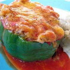 Green bell peppers are stuffed with a mixture of ground beef, onion, tomatoes, rice, and cheese then baked in a tomato soup based sauce.