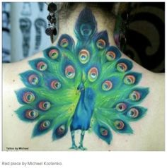 Colorful back peacock tattoo by Michael Kozlenko.