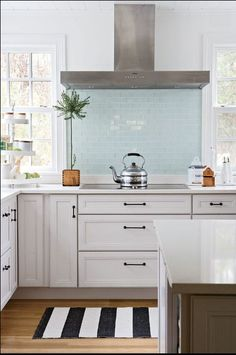 Loving the light blue subway tile and white cabinets. The range hood isn