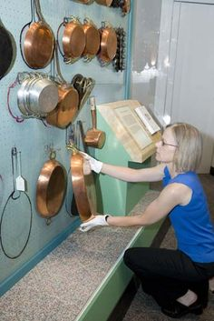 Julia Child, the genius of American cookery, had dozens of favorite pots. So many pots and pans, in fact, that her husband Paul designed a pegboard and mapping system so that each pot could be handily replaced after every use.  Here, Paula Johnson installs Julia Child's copper pots to the original mapped peg board wall at the National Museum of American History.