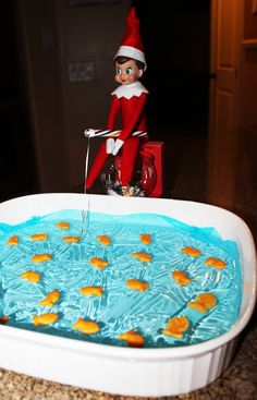 Fishing! Sitting on an ornament. Used blue Saran Wrap on top of water and goldfish crackers. The pole is made of candy cane, floss, and a paper clip.