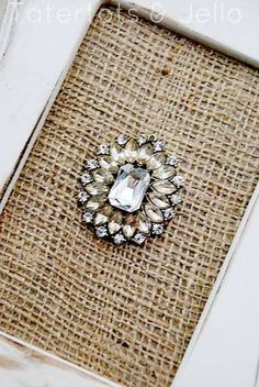 framed brooch on burlap...would be lovely with grandma's brooches