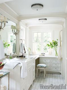 The nickel finishes on the Etoile faucet, Crystal towel rings, and Easton étagère, all by Waterworks, give the wife's side of the bathroom a soft gleam.