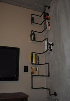 Massive bookshelf made from black iron piping.  Fixed to concrete wall in 3 places.