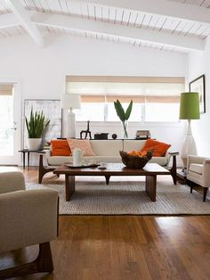 Simple & CleanSoft white walls and modern furniture make up the backbone of this Zen-inspired living room. Low-lying furniture with simple lines creates a streamlined look. Bright orange and green accents keep the space looking crisp and clean