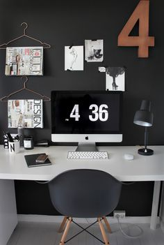 Neutral office space with dark walls - using clothes hangers to hang magazines is so clever!