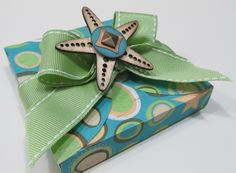 Card box, cut using the Cricut® Art Philosophy cartridge and wrapped in Sweet Leaf ribbon. Topped with a Seaside Wooden shape and a Durables square studs. #CTMH