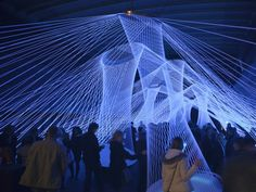 """White elastic strings pulled across the interior of a container ship formed the """"Resonate"""" installation at Frankfurt's Luminale 2012. Visitors can play with the strings, which when pulled produce sounds and lighting effects, turning the room into a collective musical instrument."""