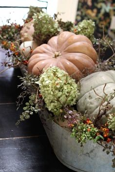 Multi-colored heirloom pumpkins combined with white pumpkin pie pumpkins, dried hydrangeas and faux bittersweet vines to create the perfect easy fall centerpiece!
