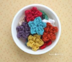 Repeat Crafter Me: Teeny Tiny Crochet Stars. Basically, picots slip stiched onto a magic ring, but very nice embellishment for other projects!