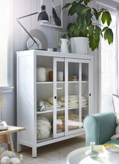 IKEA HEMNES white glass door cabinet, storing yarm and fabrics behind its sliding doors.