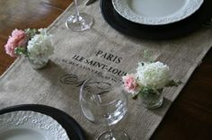 burlap table runners placed over a tablecloth with our wedding logo stenciled on, it would be very cute for our barn wedding! @Laura Jayson Blake