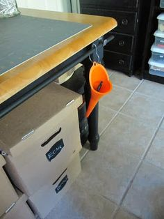 Curtain rod attached to table to hold funnels, shower curtain rings, etc. that hold tools and supplies close at hand