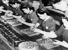 Japanese women look for possible flaws in the empty shells in a factory in Japan, on September 30, 1941. (AP Photo)
