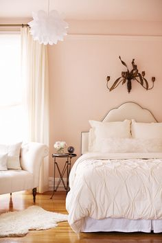 Romantic white and pink bedroom with soft pink walls paired with soft white cotton curtains. Brass wall ornament hangs over ivory leather headboard with nailhead trim paired with West Elm Organic Cotton Pintuck Duvet and white shag lumbar pillow. Ikea KNAPPA Pendant Lamp over white tufted fainting couch with pillows and directoire accent table.