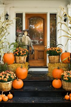 Outdoor fall decorations. I love the mums in wooden barrels and combining it with hay bails and pumpkins. I wouldn't use a scarecrow, but I like the idea of using corn stalks. How welcoming!