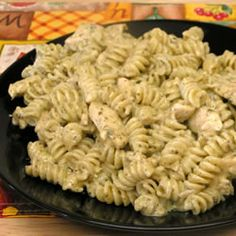 This is a quick and easy dish in which penne pasta is tossed with chicken in a simple sauce of cream, pesto and Parmesan cheese.