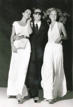 Halston designs in the 70's (he's in the middle)...figure hugging halter topped/scooped necked maxi's...one a stunning dress with flowing skirt ending at the ankle, the other tunic topped over maxi...at the ankle...white/wonderful...design motion....