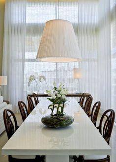 Cortinas branca, pé direito duplo, sala de jantar perfeita. Projeto de Debora Aguiar.