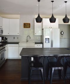 design*sponge: The all-black island brings a modern touch to this classic kitchen in Billings, Montana.
