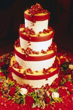 Polly Schoonmaker created a stunning four tiered fondant and buttercream wedding cake adorned with red marzipan berries.