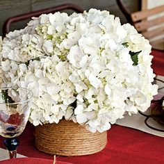 For a textural centerpiece, wrap basic glass containers in rope, securing as you go with a glue gun. Filled with white hydrangeas, these DIY vases deliver understated elegance. | SouthernLiving.com