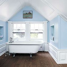Anchored with a dark hardwood floor and brightened by a large sun-filled window, the walls and ceiling of this bath look like a crisp sky. | Photo: Mark Lund | thisoldhouse.com floor, wall frames, blue walls, color, tub, old houses, bathroom ideas, vaulted ceilings, attic bathroom