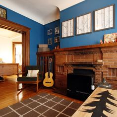 Blue walls and forest art over the fireplace.