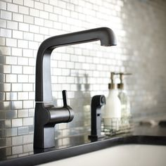 The Evoke Kitchen Faucet in Matte Black looks spectacular against the stainless steel subway tiles. Click through to see more! kitchen faucets, subway tiles