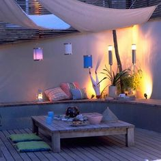 Para la terraza. Deck de madera con mesa baja, asientos en la pared.