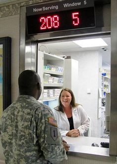 Jessica S. Pruitt, a staff pharmacist, enjoys a brief conversation with a Soldier who comes to the window booth to pick up his prescription, July 27. (Photo by Marlon J. Martin, McDonald Army Health Center, Fort Eustis, Va.)