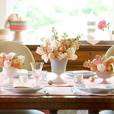 Lush centerpieces of peach stock, coral sweet pea, pink tulips, and white hyacinths set the tone for this elegant table. Add blown-out eggs, hot-glued to wooden skewers, for Easter chic. #Easter